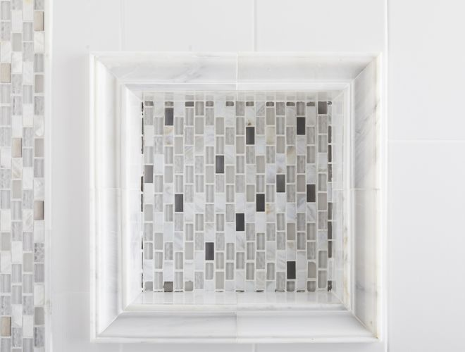 Shower wall with white marble, glass and metal mosaic accents, and recessed shelf.
