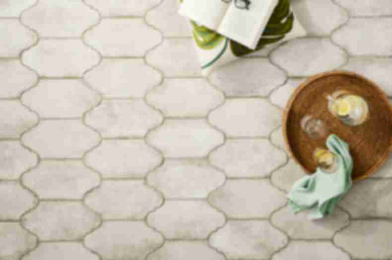 Ivory lantern shaped floor tile in a patio with plants.