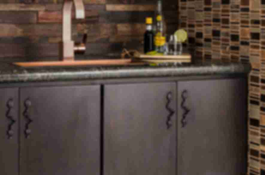 Dark brown reclaimed wood wall tile with mosaic in rustic bar area.