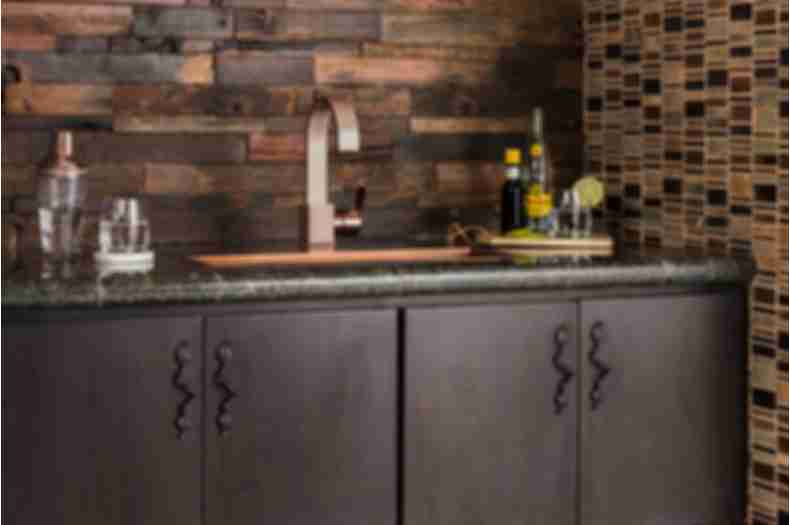 Dark brown reclaimed wood wall tile with dark brown mosaic above bar area.