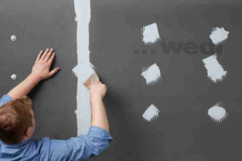 Man in process of installing wedi product.