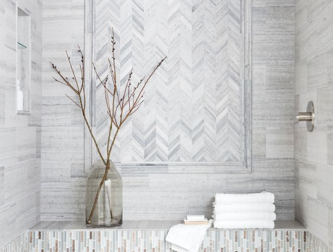 Sophisticated shower with grey limestone in chevron pattern with glass mosaic accents.
