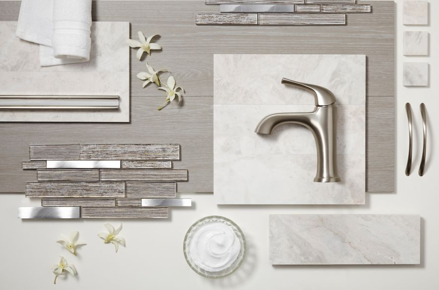 Glass and metal mosaics, grey faux wood tile, white marble tile, and trim pieces lay on a table top with a soft towel, face cream, and flowers.
