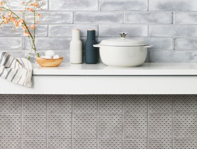 Kitchen backsplash with grey subway tile and square patterned wall tile.