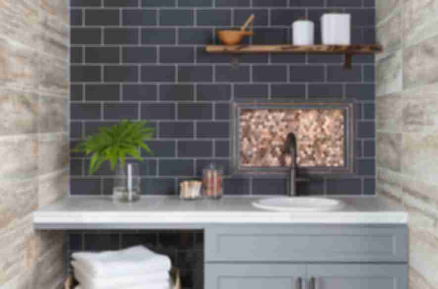 Modern farmhouse style laundry room with blue subway tile and wood-look tile on the walls and encaustic-look tile on the floor.