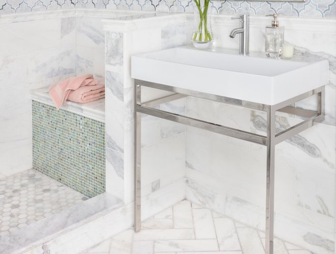 White marble bathroom with arabesque mosaic on walls and herringbone pattern on floor.