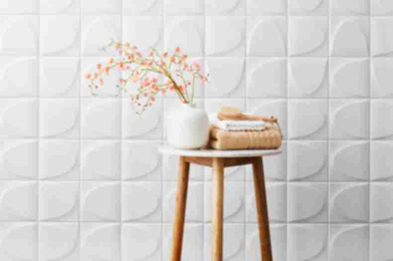White ceramic 3-D wall tile in spa-like bathroom.