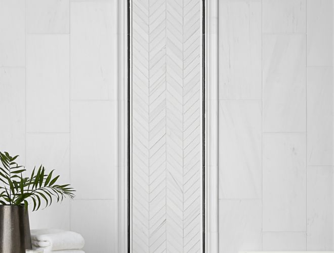 White marble wall tile with chevron accent design and black trim in modern bathroom.