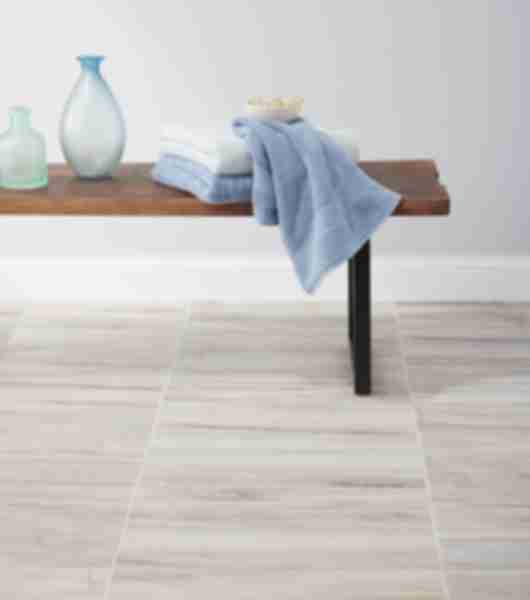 Laundry area with brown and ivory textured floor tile.