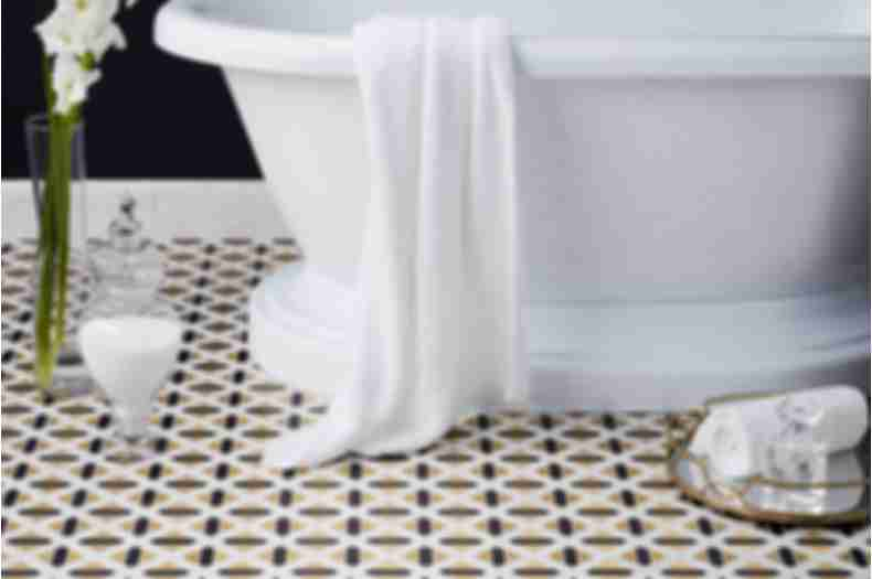 Gold black and white geometric floor tile in glamorous bathroom with freestanding tub.