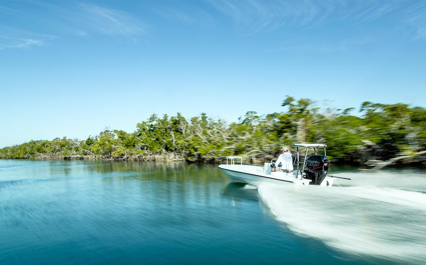Person Mercury 60r outboard motor white boat lake