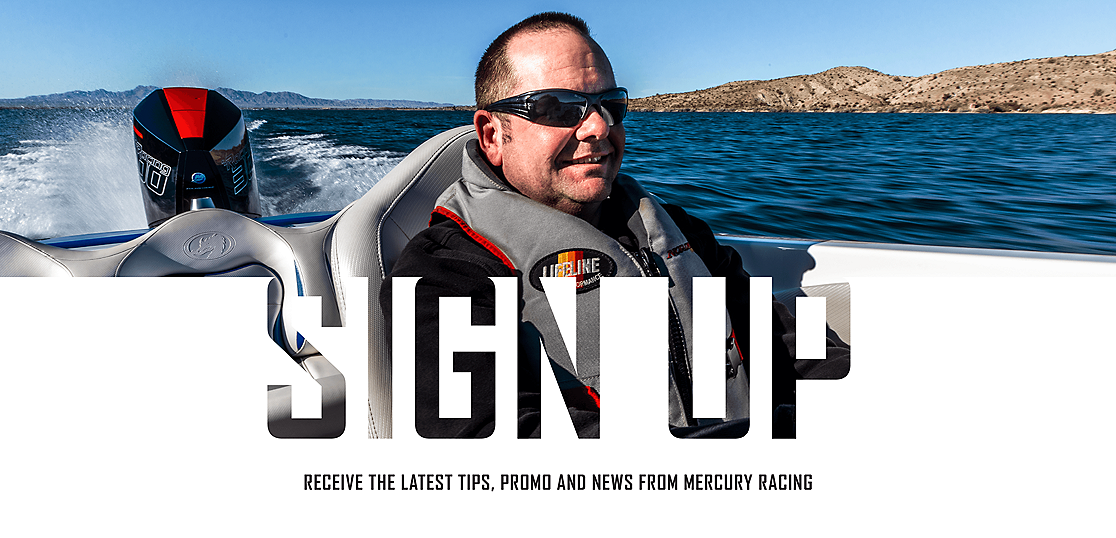 An image with a man smiling will driving a boat with a black and red Mercury Racing 300R outboard with water in the background.