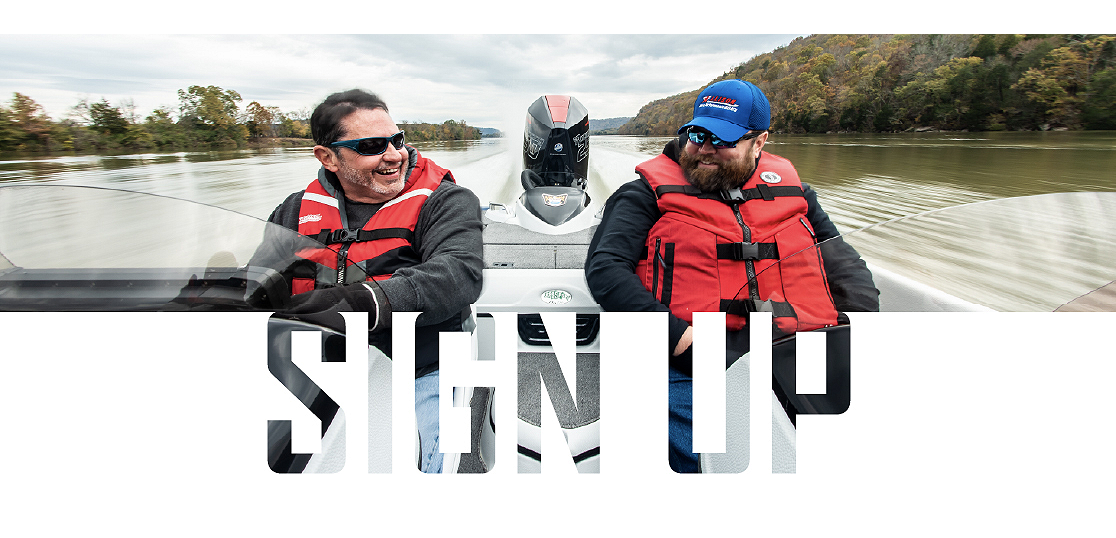 Two men wearing life preservers and sunglasses shown from the front with a black and red Mercury outboard engine attached to the stern of a white boat on a lake.