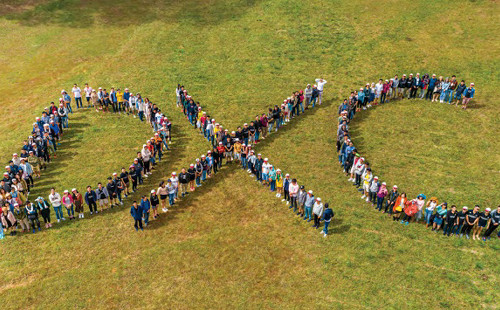 people standing to form the letters DXC