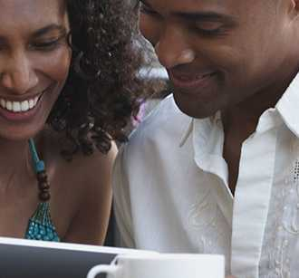 Couple in outdoor café making an ecommerce purchase on a tablet