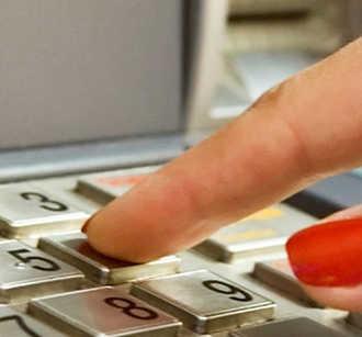 Woman entering pin at ATM