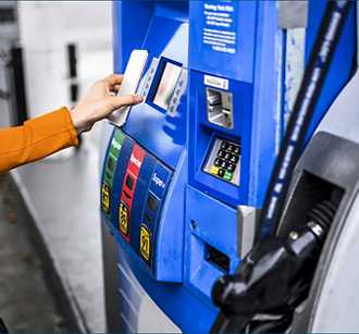 Woman paying with phone at gas pump
