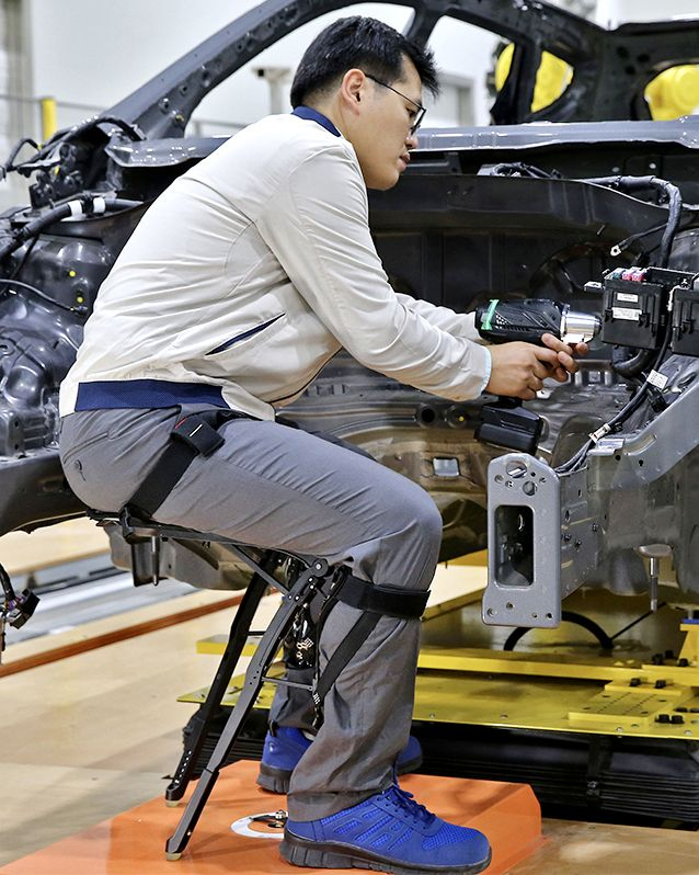 Hyundai employee sitting with a Hyundai Chairless Exoskeleton as he works on a car