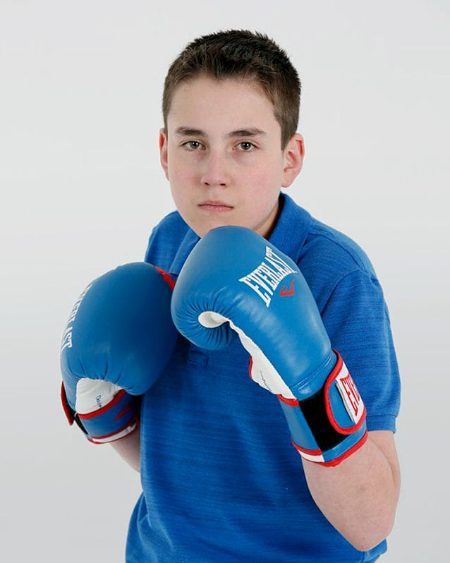 Portrait of Carter holding his hands up with blue boxing gloves wearing a blue polo