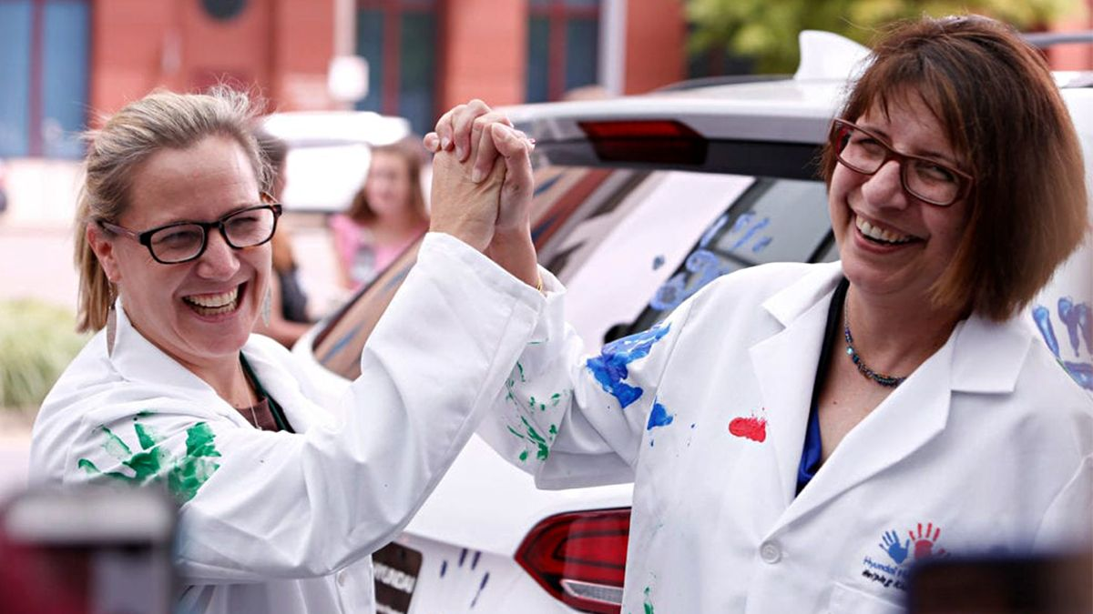 Two female doctors wearing Hope on Wheels lab robes with different color paint stains high five during Hope on Wheels event