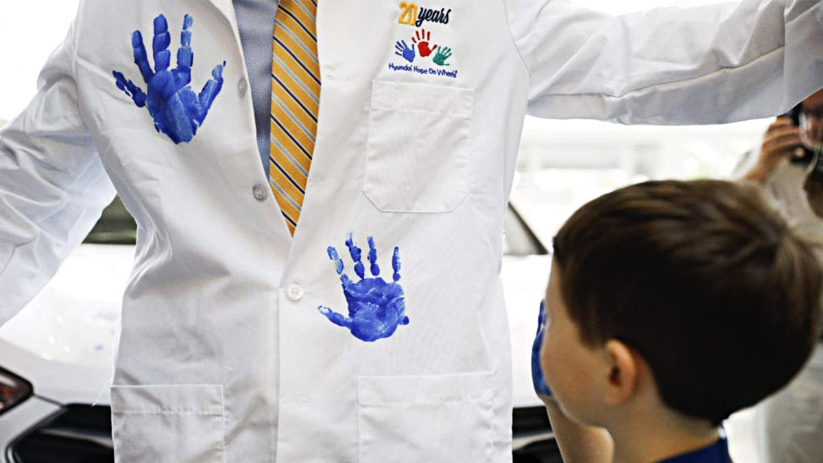 Male doctor in Hope on Wheels lab coat has two blue handprints stamped on it by a little boy with blue paint in his hand