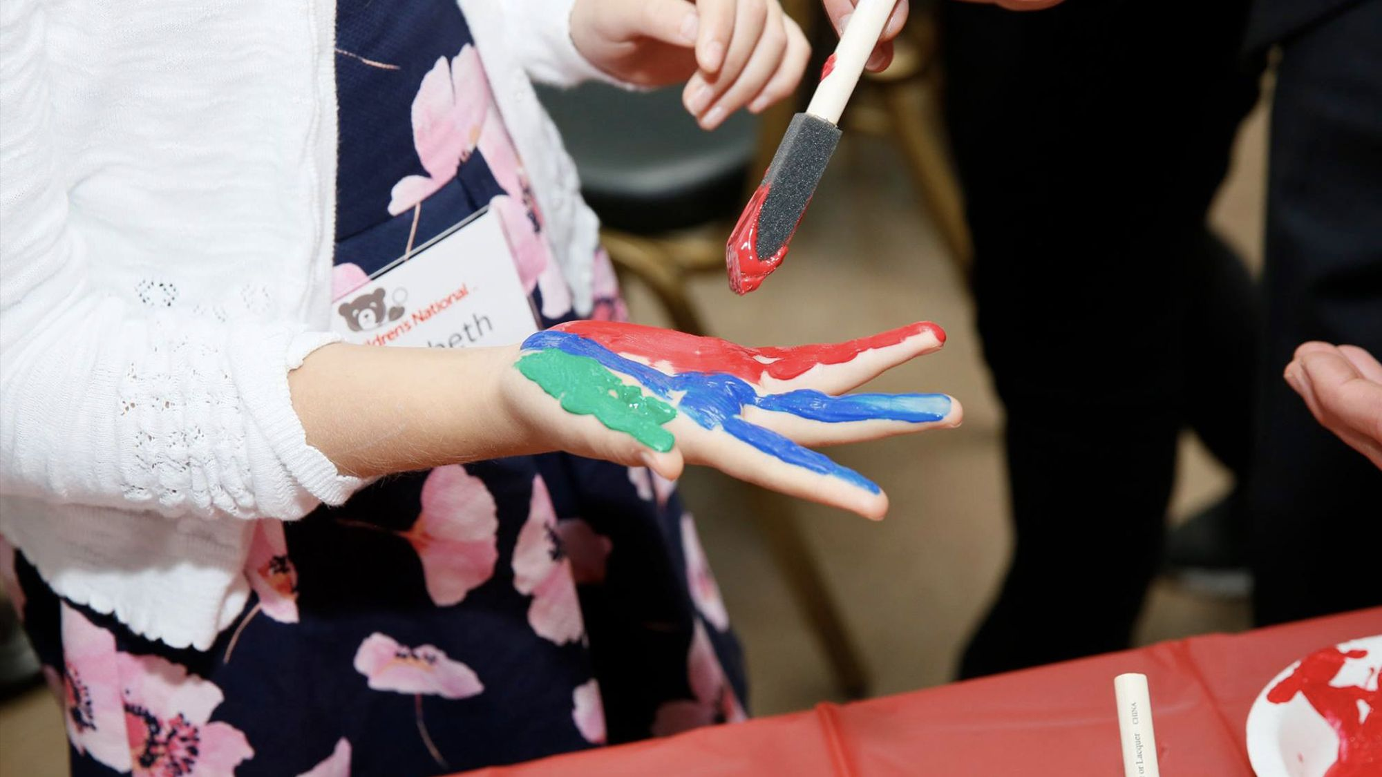 National Youth Ambassador Elizabeth puts red blue and green paint on her hand at a Hope on Wheels event