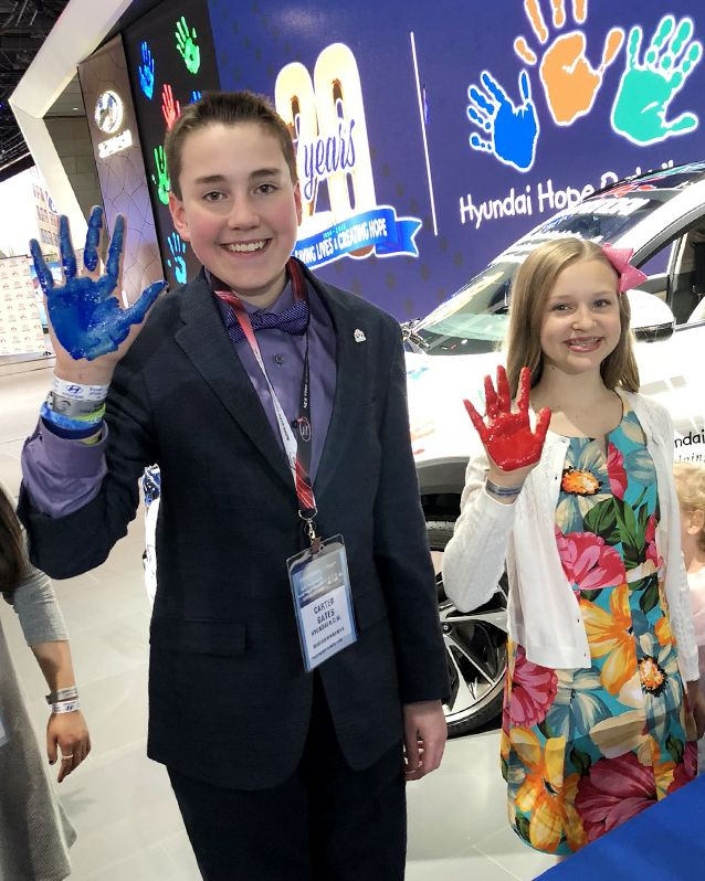 National Youth Ambassadors Carter and Elizabeth show their hands with blue and red paint during at a Hope on Wheels event