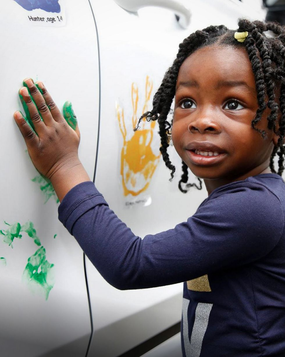 Little girl stamps her handprint with green paint on a Hyundai car during a Hope on Wheels event