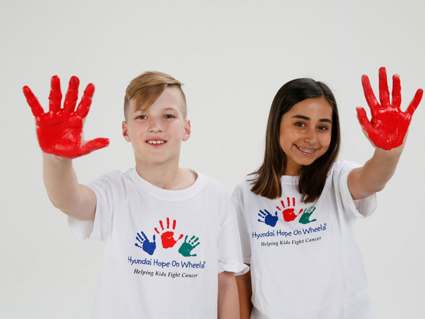 National Youth Ambassadors Jordyn and Alex show their red hands for Hope on Wheels