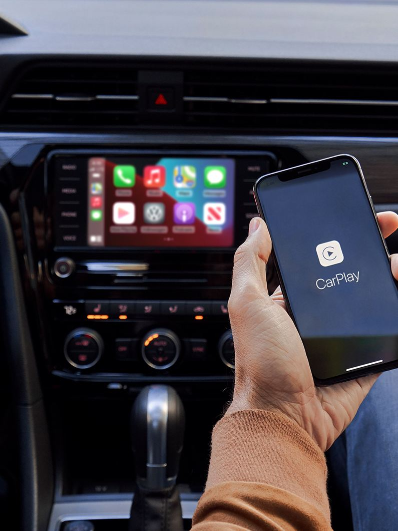 The hand of a person sitting in the front passenger seat of a VW holds their iPhone as it's connected to App-Connect