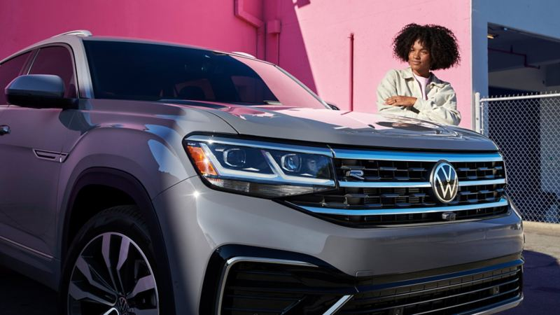 A woman proudly looks at her Atlas Cross Sport shown in Pure Gray.