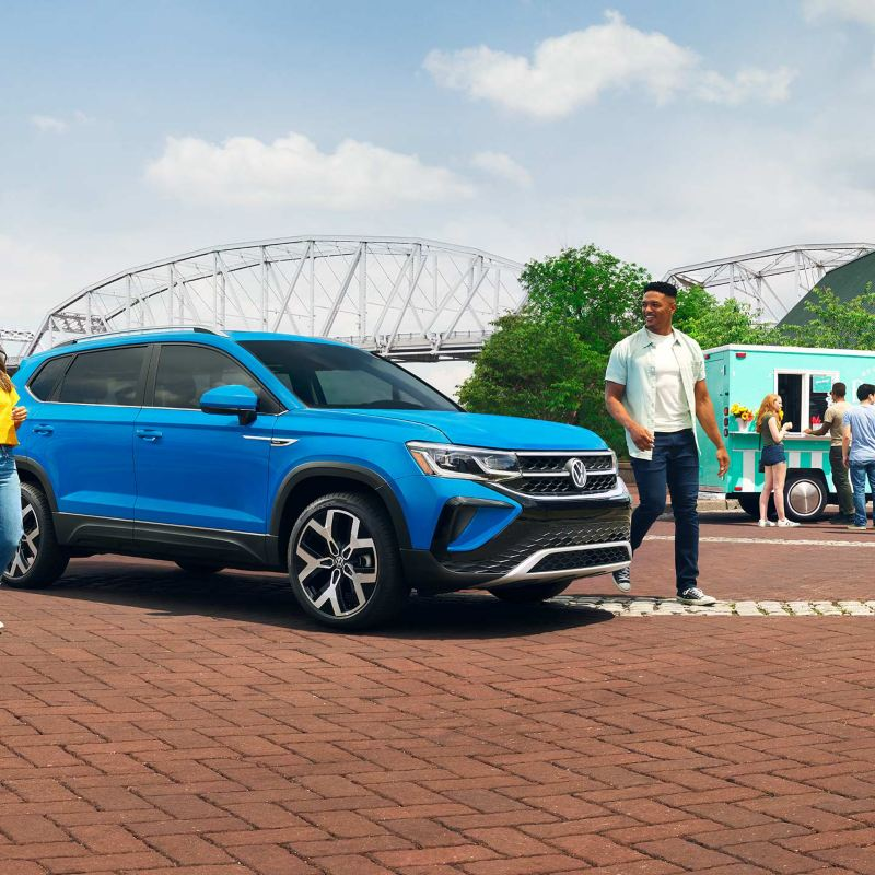 A father and daughter leave their VW parked in the driveway and head in the front door.