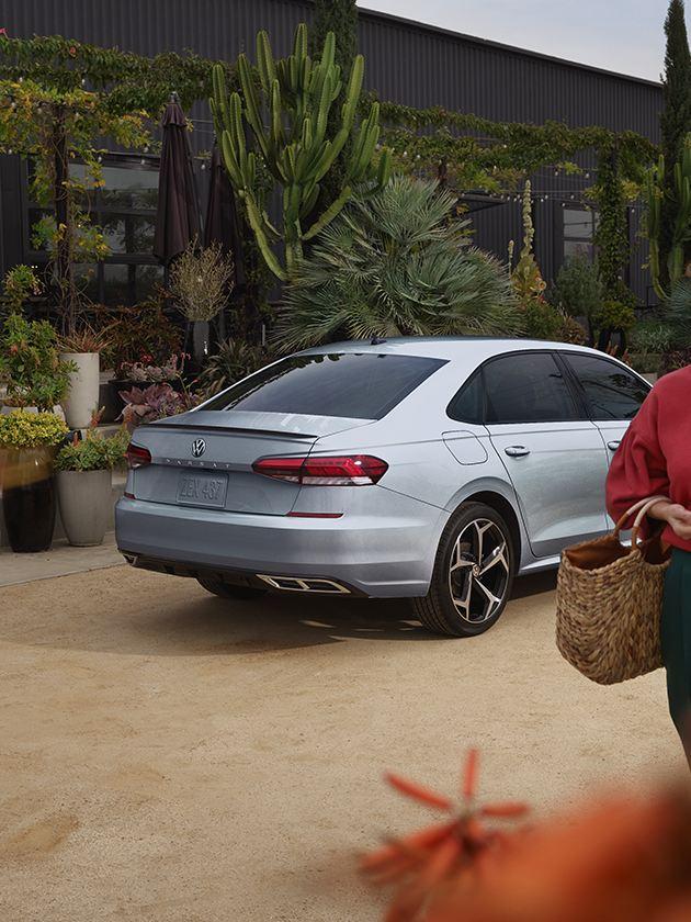 Una mujer camina junto a un VW Passat en Reflex Silver Metallic estacionado.
