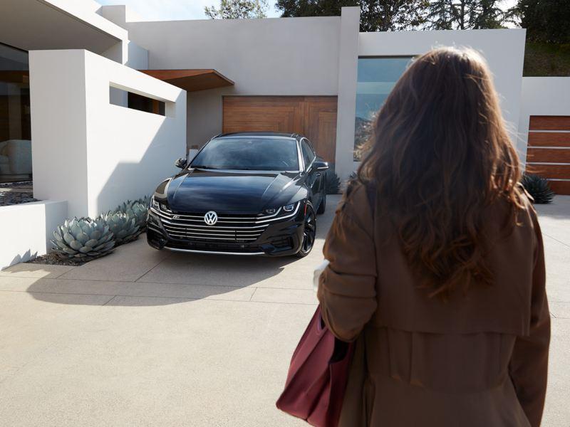 Una mujer mira el VW Arteon estacionado frente a un hogar moderno.