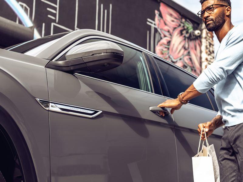 Un hombre se dirige a abrir la puerta del conductor de un VW Atlas Cross Sport con una bolsa de compras en la mano.