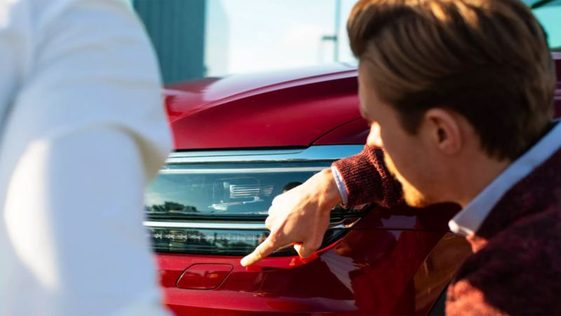 A well-dressed inspection agent points to a blemish underneath the driver's side headlight of a tornado red Golf SportWagen.