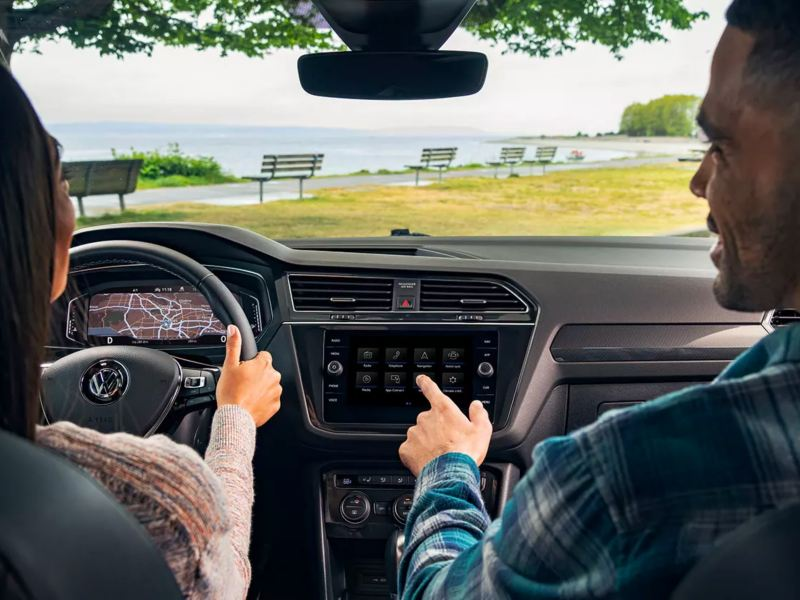 Young couple views scenic lake through the windshield of their Volkswagen Tiguan—complete with impressive interior tech.