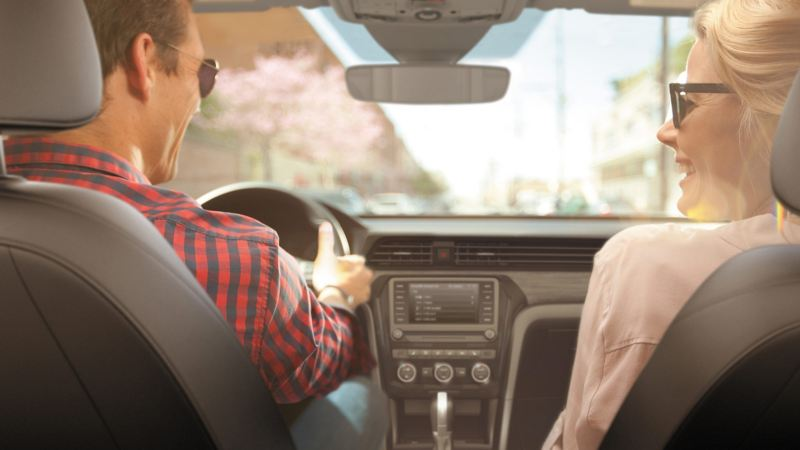 A joyful couple frames an interior view of the media touchscreen, controls, and gear shift in a Volkswagen vehicle.