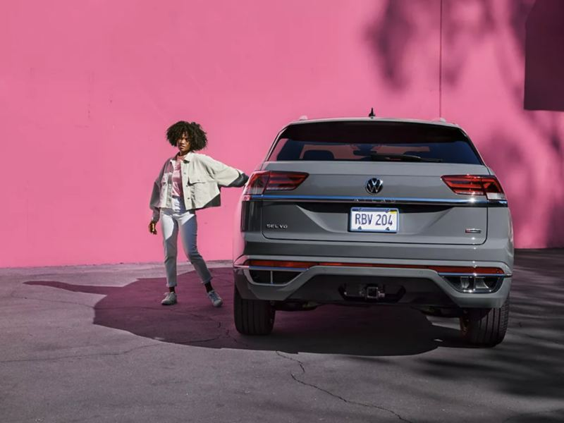 A hot pink wall backgrounds a young woman's bold exit from her platinum gray metallic Volkswagen Atlas Cross Sport.