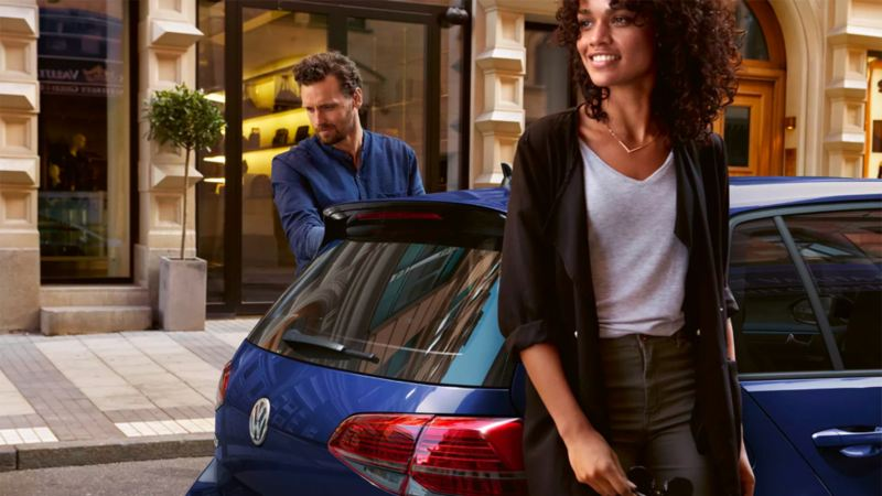 A debonair couple leans against their parked silk blue metallic Volkswagen Golf, ready to take on the town.