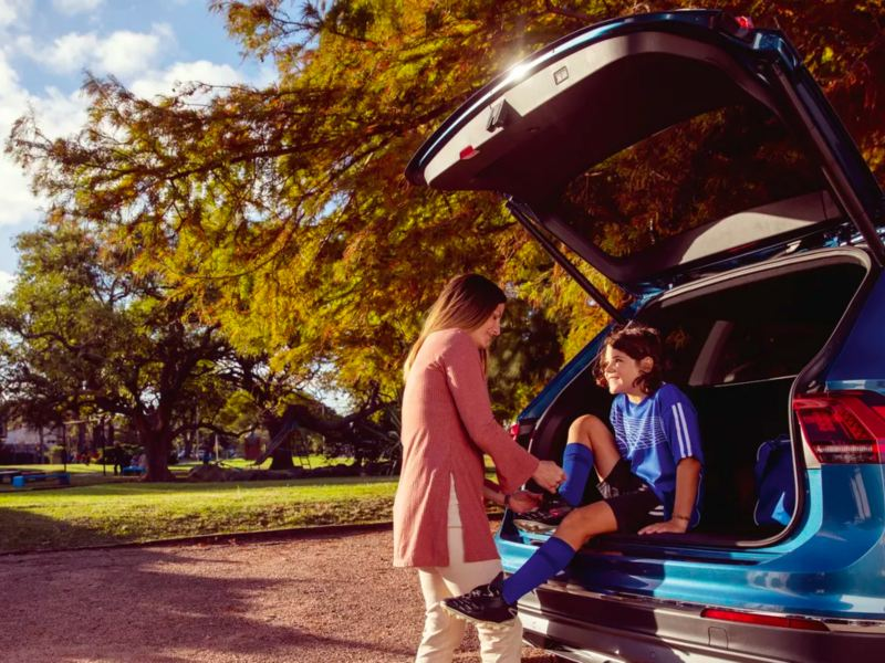 A child in the open trunk of a pacific blue metallic Volkswagen Atlas shares a smile while mother ties their soccer cleats.