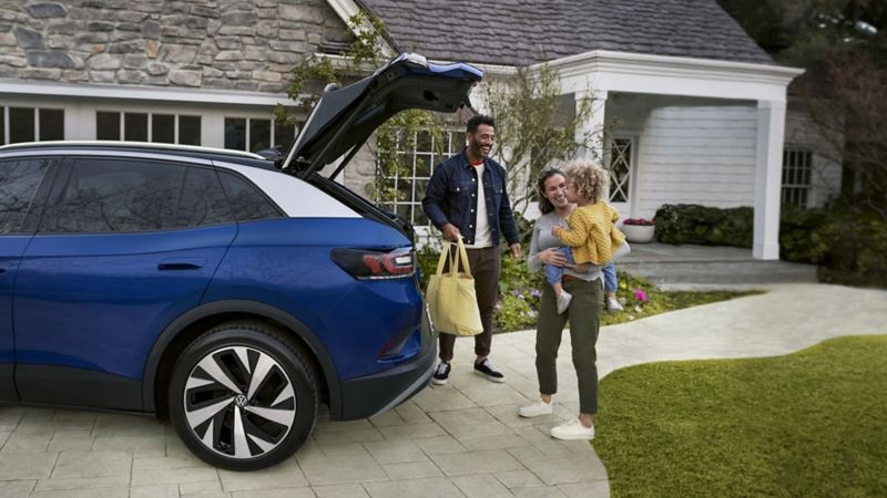 A family of three unloads bags from the trunk of their dusk blue metallic Volkswagen ID.4, parked on their large stone driveway.