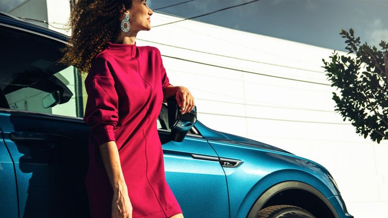 Confident woman with voluminous hair in fuchsia mock neck dress leans against a blue silk metallic Volkswagen Tiguan R-Line.