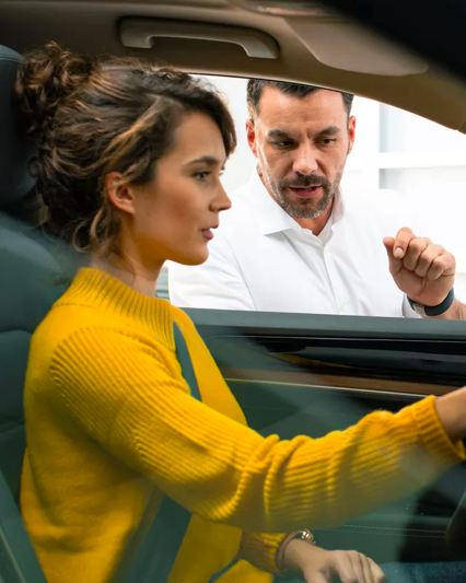 A young woman in a mustard yellow sweater sits in the driver's seat of a Volkswagen Tiguan with sales manager.
