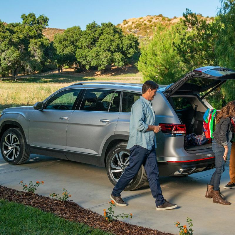A family of four unloading backpacks from the trunk of a platinum gray metallic Volkswagen Atlas, accompanied by family dog.