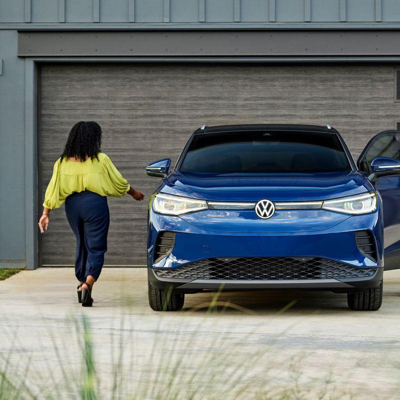 Un hombre y una mujer en lados opuestos de un vehículo eléctrico VW ID.4 en Dusk Blue Metallic estacionado frente a un garaje residencial.