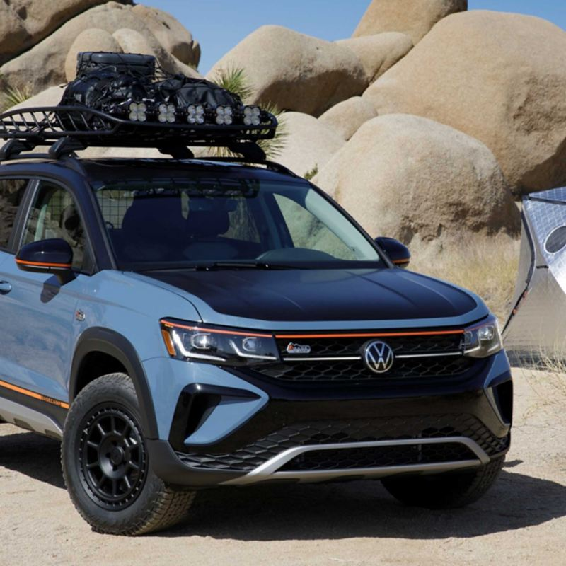 The Taos Basecamp Concept vehicle in Waimea Blue with gloss black trim elements, matte black hood and roof, and orange accents in outdoor setting with boulders and tent in background.