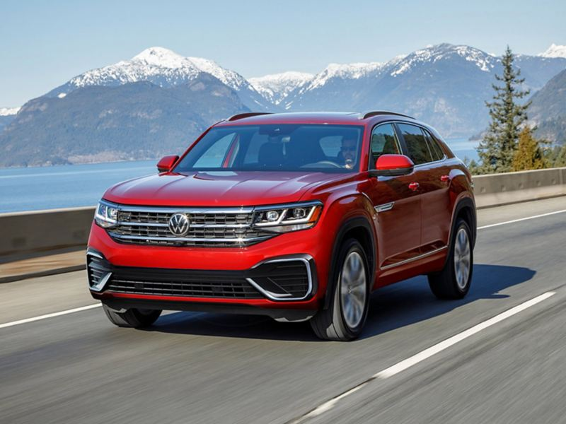 The Atlas Cross Sport in Aurora Red Metallic as seen from the front driving alongside a mountain and lake.