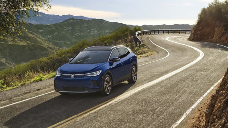 A dusk blue metallic Volkswagen ID.4 curves along an open road surrounded by a verdant, hilly landscape.