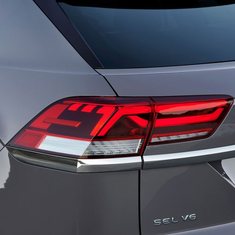 A platinum gray metallic Volkswagen Atlas V6 SEL is angled and cropped to show its rear driver's side led lights.